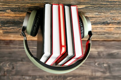 Photo of a stack of books with a pair of headphones