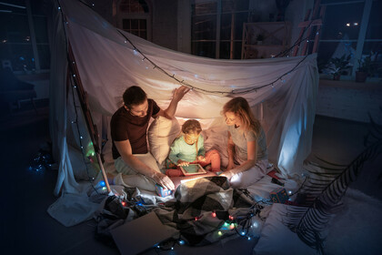 Family reading together at night in a makeshft fort