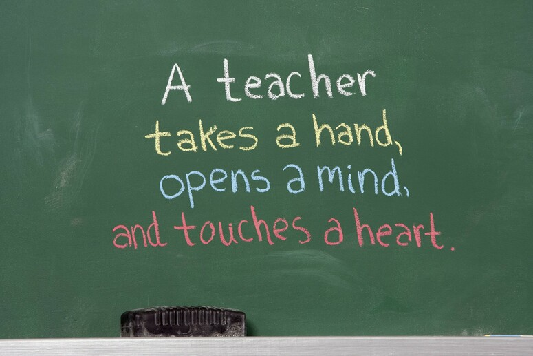 "Photo of a blackboard with the phrase ""A teacher takes a hand, opens a mind, and touches a heart"""